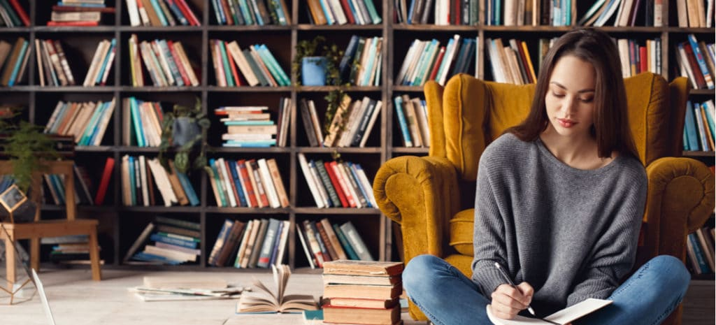 Woman writing in notebook sitting in front of bookcase